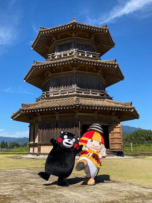くまモンところう君 後ろは鞠智城のシンボル・八角形鼓楼(ころう)