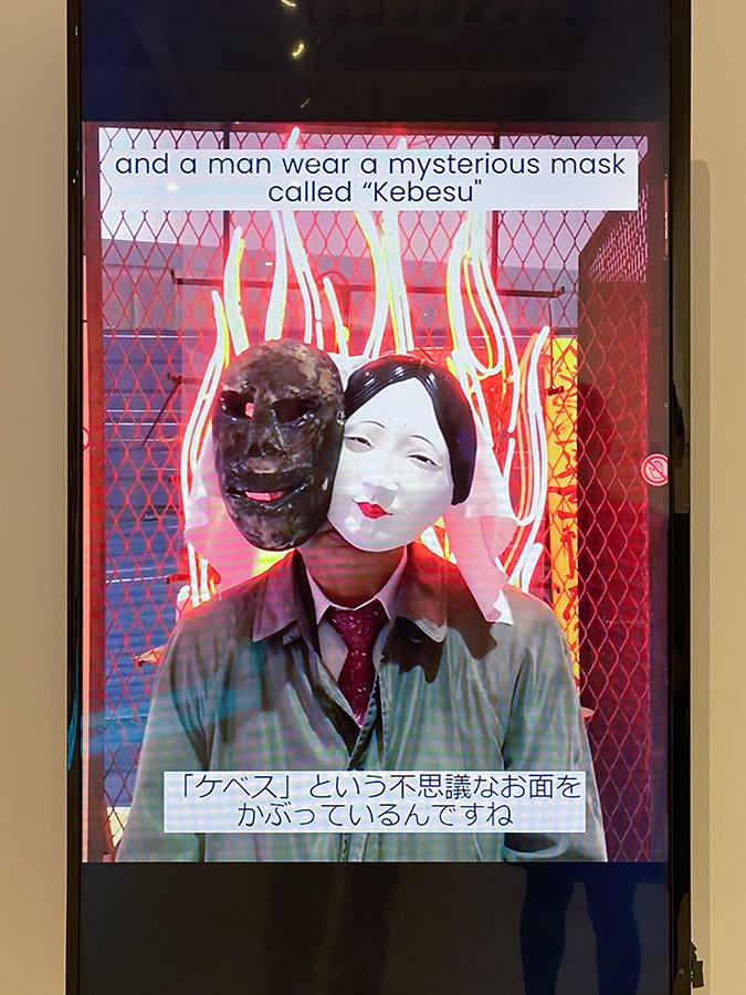 仮面や衣装を身に着けて解説するのは、ディレクターの北川フラム